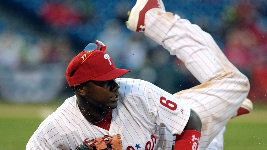 Philadelphia Phillies first baseman Ryan Howard dives to touch first base forcing out Kansas City Royals outfielder Jarrod Dyson after he hit a ground ball during their baseball game Friday, April 5, 2013, in Philadelphia. (AP Photo/The Express-Times, Matt Smith)