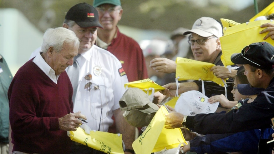 ADVANCE FOR WEEKEND EDITIONS, APRIL 6-7 - FILE - In this April 6, 2004, file photo, four-time Masters champion Arnold Palmer signs autographs for fans as he arrives for practice for the Masters golf tournament at the Augusta National Golf Club in Augusta, Ga.  Palmer makes sure every fan can read his name. And like so many other aspects of his golfing career, his influence spans generations. (AP Photo/Amy Sancetta, File)