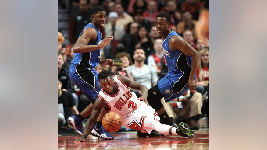 Chicago Bulls' Nate Robinson slips and is called for traveling during the second quarter against the Orlando Magic in an NBA basketball game on Friday, April 5, 2013 in Chicago. The Magic defenders are E'Twaun Moore, left, and Doron Lamb. (AP Photo/Charles Cherney)