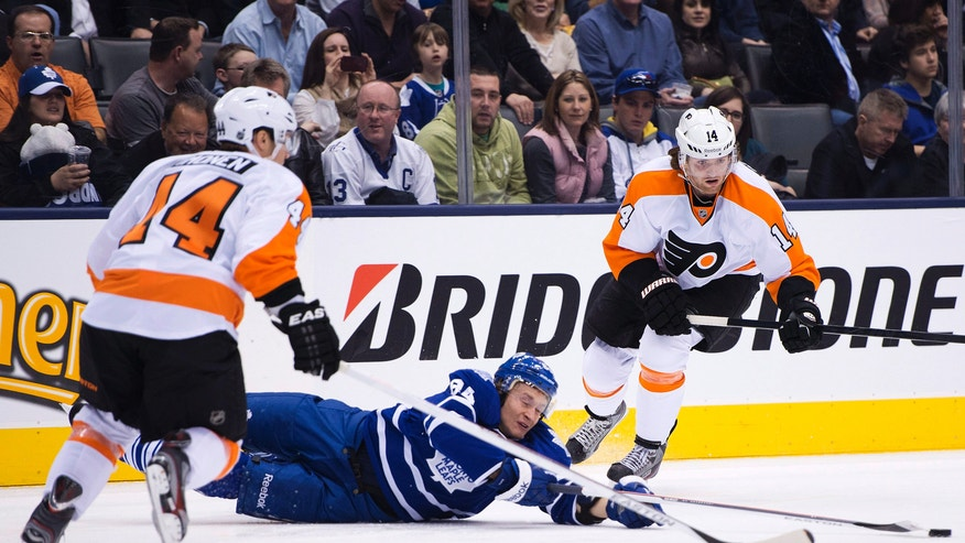 Philadelphia Flyers teammates Kimmo Timonen, left, and Sean Couturier, right, take out Toronto Maple Leafs forward Mikhail Grabovski, center, during the second period of an NHL hockey game in Toronto on Thursday, April 4, 2013. (AP Photo/The Canadian Press, Nathan Denette)