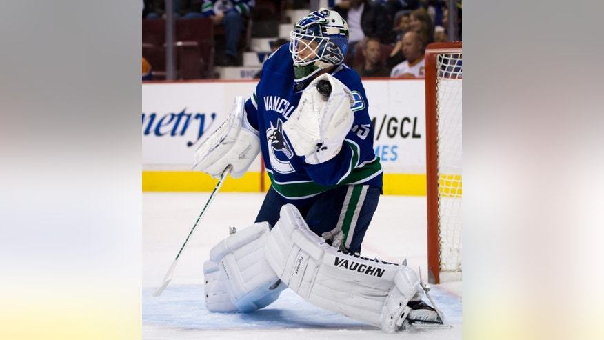 Vancouver Canucks' goalie Cory Schneider makes a glove save against the Edmonton Oilers during the first period of an NHL hockey game Thursday, April 4, 2013, in Vancouver, British Columbia. (AP Photo/The Canadian Press, Darryl Dyck)