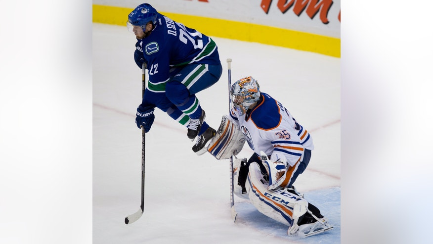 Vancouver Canucks' Daniel Sedin, of Sweden, jumps in front of goalie Edmonton Oilers' goalie Nikolai Khabibulin, of Russia, during the second period of an NHL hockey game Thursday, April 4, 2013, in Vancouver, British Columbia. (AP Photo/The Canadian Press, Darryl Dyck)