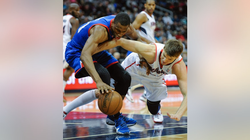 Philadelphia 76ers forward Thaddeus Young, left, and Atlanta Hawks forward Kyle Korver, right, battle for a loose ball during the first half of a basketball game, Friday, April 5, in Atlanta. (AP Photo/John Amis)