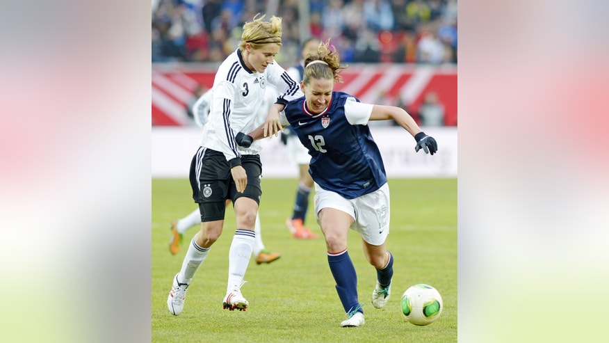 Germany's Saskia Bartusiak, left, and Lauren Cheney of the U.S., right, challenge for the ball during the international friendly women's soccer match between Germany and the United States in Offenbach, central Germany, on Friday, April 5, 2013. (AP Photo/Jens Meyer)