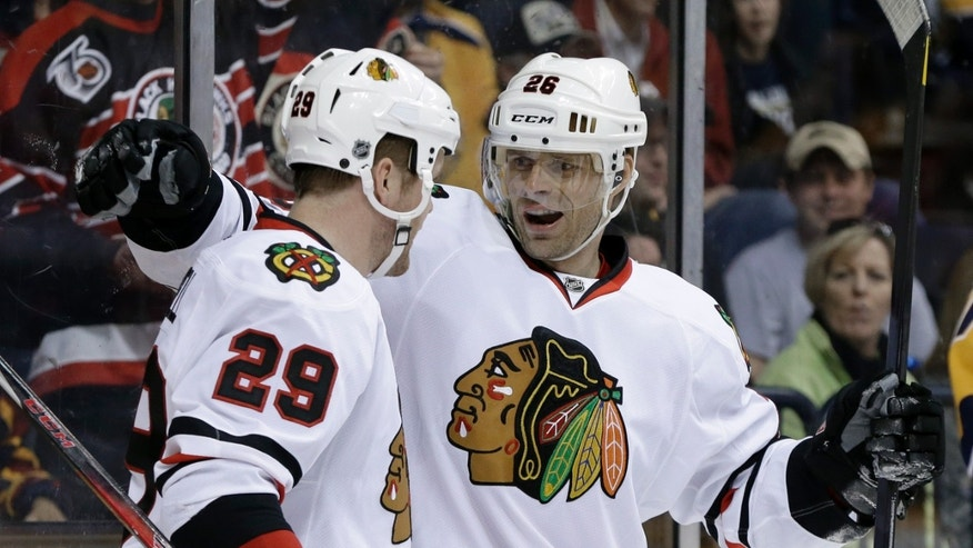 Chicago Blackhawks left wing Bryan Bickell (29) is congratulated by Michal Handzus (26) after Bickell scored against the Nashville Predators in the first period of an NHL hockey game on Saturday, April 6, 2013, in Nashville, Tenn. (AP Photo/Mark Humphrey)