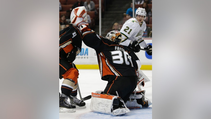 Anaheim Ducks goalie Viktor Fasth, right, of Sweden, makes a save in front of Cam Fowler as Dallas Stars' Loui Eriksson, background right, watches during the first period of an NHL hockey game in Anaheim, Calif., Friday, April 5, 2013. (AP Photo/Jae C. Hong)