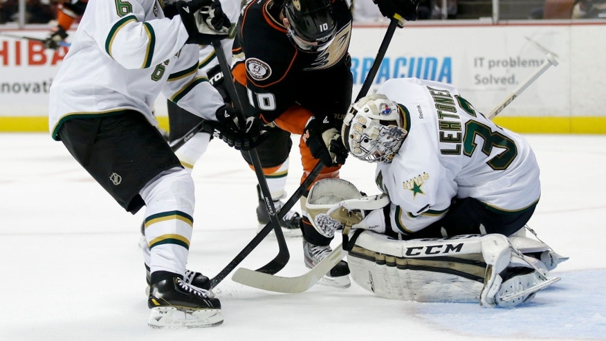 Anaheim Ducks' Corey Perry, center, tries to score against Dallas Stars goalie Kari Lehtonen, right, of Finland, as Stars' Trevor Daley watches during the second period of an NHL hockey game in Anaheim, Calif., Friday, April 5, 2013. (AP Photo/Jae C. Hong)