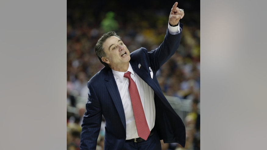 Louisville head coach Rick Pitino speaks to players during the first half of the NCAA Final Four tournament college basketball semifinal game against Wichita State, Saturday, April 6, 2013, in Atlanta. (AP Photo/David J. Phillip)