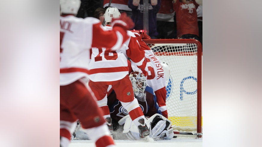 Detroit Red Wings center Pavel Datsyuk (13) falls on top of Colorado Avalanche goalie Jean-Sebastien Giguere (35) after Datsyuk scored the game-winning goal in overtime of an NHL hockey game Friday, April 5, 2013, in Denver. Detroit won 3-2. (AP Photo/Joe Mahoney)