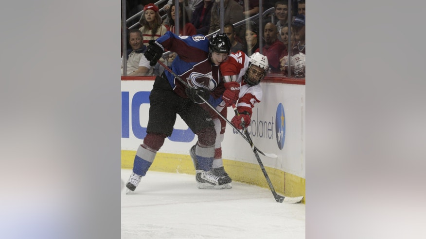 Detroit Red Wings defenseman Kyle Quincey (27) covers the puck against Colorado Avalanche center Matt Duchene (9) in the first period of an NHL hockey game on Friday, April 5, 2013, in Denver. (AP Photo/Joe Mahoney)