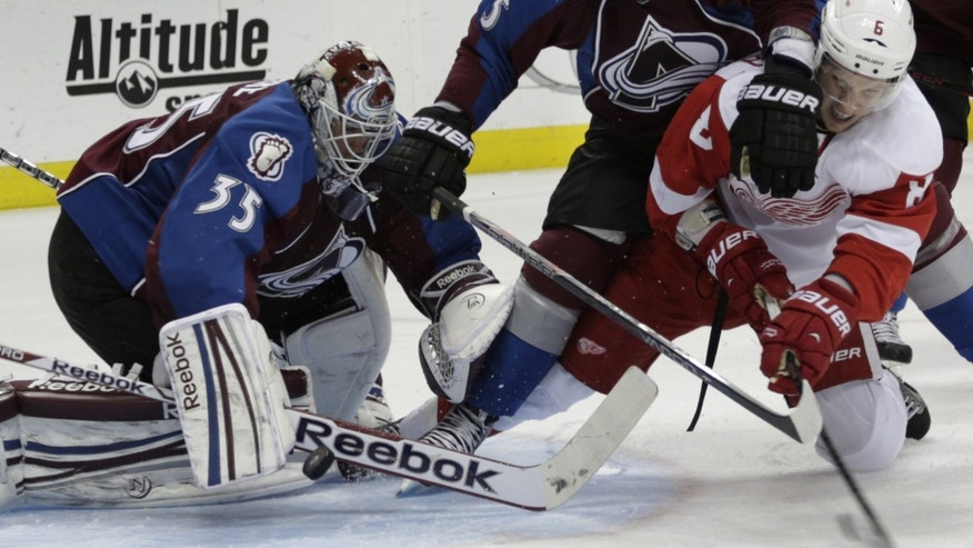 Colorado Avalanche goalie Jean-Sebastien Giguere (35) lunges for the puck as Avalanche defenseman Shane O'Brien (5) tries to keep Detroit Red Wings left wing Justin Abdelkader (8) away in the second period of an NHL hockey game on Friday, April 5, 2013, in Denver. (AP Photo/Joe Mahoney)