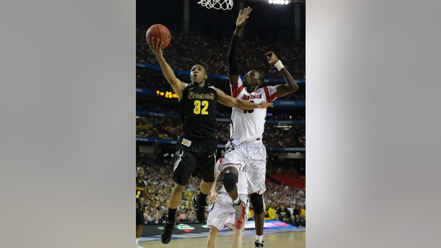 Wichita State's Tekele Cotton (32) heads to he hoop as Louisville's Gorgui Dieng (10) during the first half of the NCAA Final Four tournament college basketball semifinal game Saturday, April 6, 2013, in Atlanta. (AP Photo/David J. Phillip)