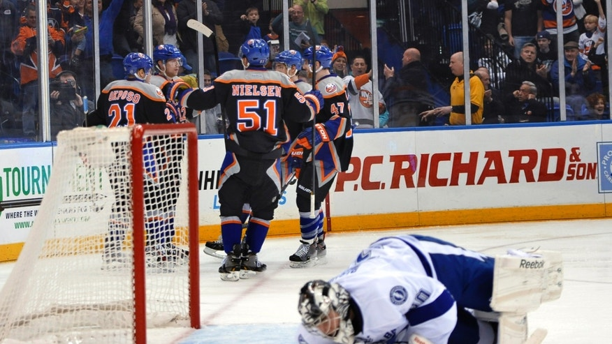 New York Islanders' Kyle Okposo (21), Frans Nielsen (51) and Andrew MacDonald (47) celebrate Josh Bailey's goal against Tampa Bay Lightning goalie Ben Bishop, foreground, in the second period of an NHL hockey game Saturday, April 6, 2013, at Nassau Coliseum in Uniondale, N.Y. (AP Photo/Kathy Kmonicek)