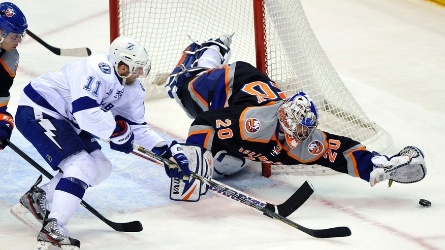 New York Islanders goalie Evgeni Nabokov (20) stretches to block a shot on goal by Tampa Bay Lightning Tom Pyatt (11) during the first period of an NHL hockey game Saturday, April 6, 2013, at Nassau Coliseum in Uniondale, N.Y. (AP Photo/Kathy Kmonicek)