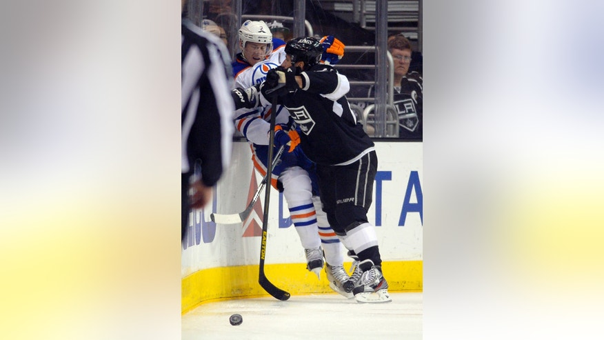 Los Angeles Kings center Jarret Stoll, right, checks Edmonton Oilers defenseman Jeff Petry into the boards during the second period of an NHL hockey game, Saturday, April 6, 2013, in Los Angeles. (AP Photo/Mark J. Terrill)