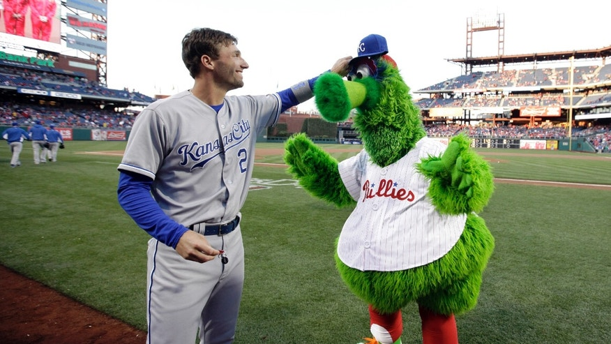 Kansas City Royals' Jeff Francoeur, left, makes the Philadelphia Phillies' mascot, the Phillie Phanatic wear a Royals hat to earn back the stolen keys to the mascot's all-terrain vehicle, before a baseball game, Saturday, April 6, 2013, in Philadelphia. (AP Photo/Matt Slocum)