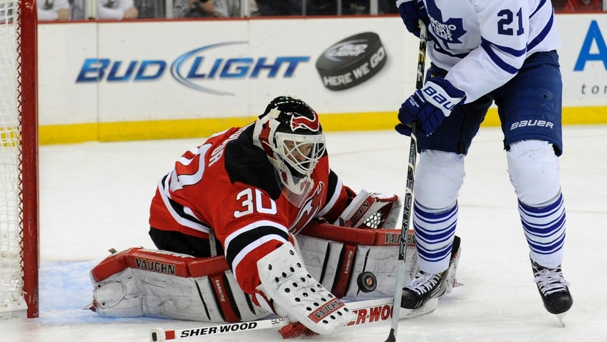 New Jersey Devils goaltender Martin Brodeur, left, makes a save as Toronto Maple Leafs' James van Riemsdyk looks for the rebound during the first period of an NHL hockey game, Saturday, April 6, 2013, in Newark, N.J. (AP Photo/Bill Kostroun)