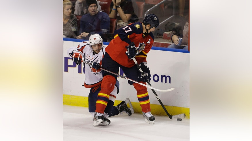 Washington Capitals' Mathieu Perreault (85) tries to get the puck from Florida Panthers' Filip Kuba (17) during the second period of an NHL hockey game in Sunrise, Fla., Saturday, April 6, 2013. (AP Photo/J Pat Carter)
