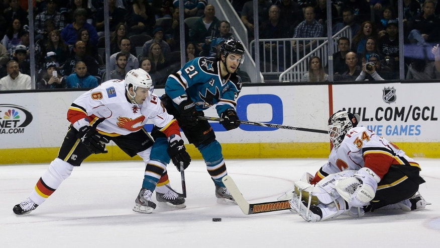 Calgary Flames goalie Miikka Kiprusoff (34), from Finland, and defenseman Cory Sarich (6) defend a shot by San Jose Sharks left wing T.J. Galiardi (21) during the first period of an NHL hockey game in San Jose, Calif., Friday, April 5, 2013. (AP Photo/Jeff Chiu)