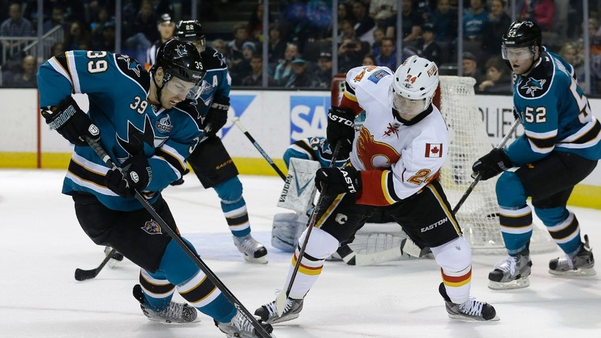 San Jose Sharks center Logan Couture (39) tries to control the puck in front of Calgary Flames left wing Jiri Hudler (24), from Czech Republic, during the second period of an NHL hockey game in San Jose, Calif., Friday, April 5, 2013. (AP Photo/Jeff Chiu)