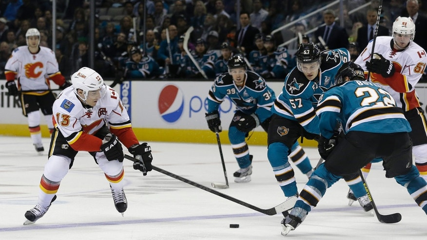 Calgary Flames left wing Mike Cammalleri (13) skates against San Jose Sharks center Tommy Wingels (57) and center Scott Gomez (23) during the second period of an NHL hockey game in San Jose, Calif., Friday, April 5, 2013. (AP Photo/Jeff Chiu)