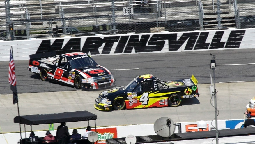 Driver Jeb Burton (4) drives past a spinning Ron Hornaday Jr. (9) during the Kroger 250 NASCAR Truck series auto race at Martinsville Speedway, Saturday, April 6, 2013, in Martinsville, Va. (AP Photo/Steve Helber)