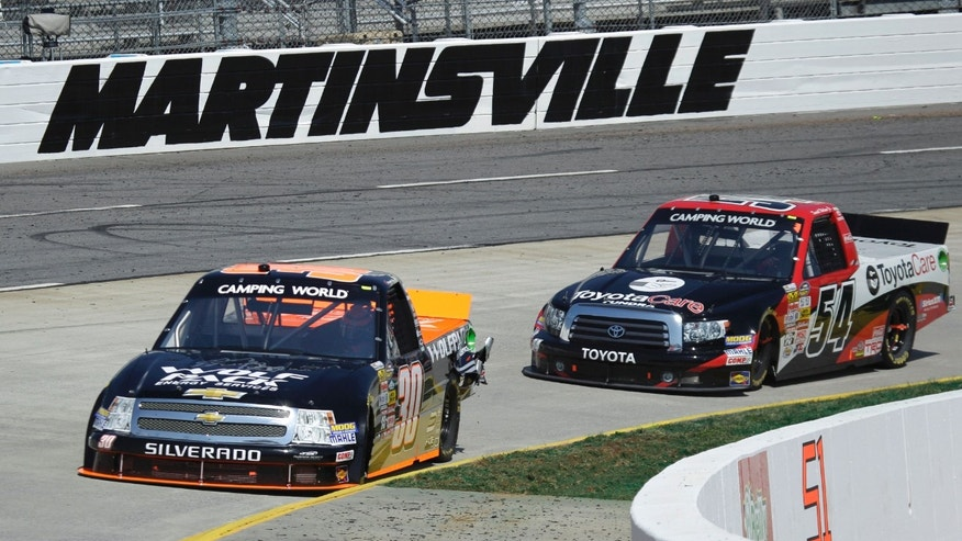 Drivers Nelson Piquet Jr. (30) and Darrell Wallace Jr. (54) make the curve in turn four during the Kroger 250 NASCAR Truck series auto race at Martinsville Speedway in Martinsville, Va., Saturday, April 6, 2013. (AP Photo/Steve Helber)