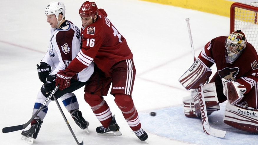 Phoenix Coyotes goalie Mike Smith, right, makes a save on a shot as Colorado Avalanche left winger Cody McLeod, left, is checked by Coyotes defenseman Rosislav Klesla, center, of the Czech Republic, as McLeod sets a screen in front of Smith in the second period of NHL hockey game, Saturday, April 6, 2013, in Glendale, Ariz. (AP Photo/Paul Connors)