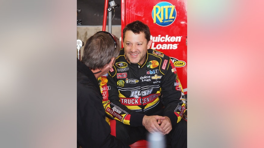 Driver Tony Stewart talks with a crew member in the garage after practice for Sunday's NASCAR Sprint Cup series auto race at Martinsville Speedway in Martinsville, Va., Saturday, April 6, 2013. (AP Photo/Steve Sheppard)