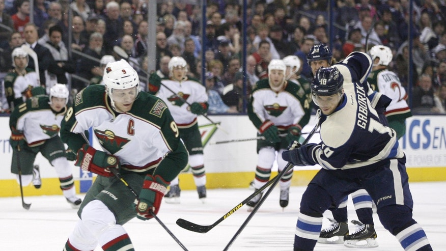Columbus Blue Jackets' Marian Gaborik (10), right, of Slovakia, tries to get the puck from Minnesota Wild's Mikko Koivu, (9), of Finland, in the second period of an NHL hockey game on Sunday, April 7, 2013, in Columbus, Ohio. (AP Photo/Mike Munden)