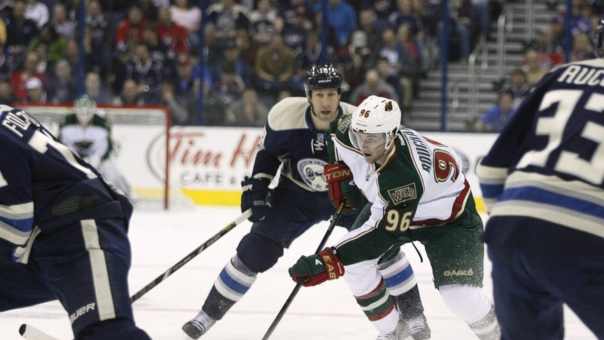 Minnesota Wild's Pierre-Marc Bouchard (96) weaves through the defense of the Columbus Blue Jackets in the first period of an NHL hockey game on Sunday, April 7, 2013, in Columbus, Ohio. (AP Photo/Mike Munden)