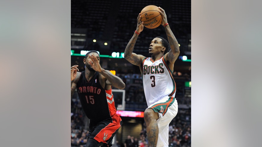 Toronto Raptors' Amir Johnson (15) defends as Milwaukee Bucks' Brandon Jennings (3) drives to the basket during the second half of an NBA basketball game Saturday, April 6, 2013, in Milwaukee. (AP Photo/Jim Prisching)