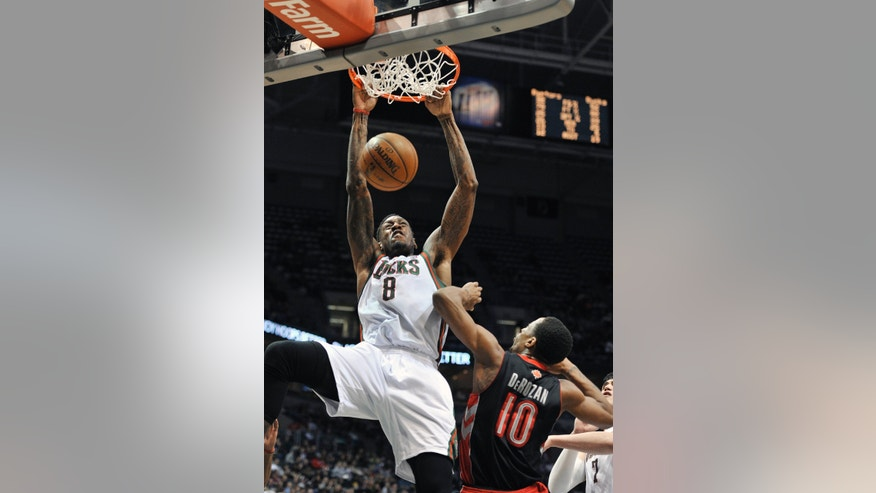 Milwaukee Bucks' Larry Sanders (8) dunks over Toronto Raptors' DeMar DeRozan (10) during the second half of an NBA basketball game Saturday, April 6, 2013, in Milwaukee. (AP Photo/Jim Prisching)