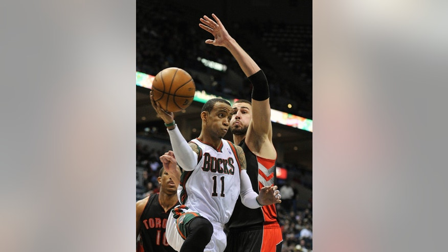Milwaukee Bucks' Monta Ellis (11) drives around Toronto Raptors' Jonas Valanciunas during the second half of an NBA basketball game Saturday, April 6, 2013, in Milwaukee. (AP Photo/Jim Prisching)