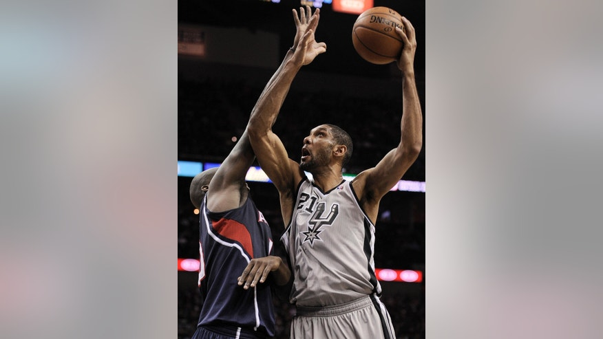 San Antonio Spurs' Tim Duncan, right, shoots over Atlanta Hawks' Johan Petro, of France, during the first half of an NBA basketball game, Saturday, April 6, 2013, in San Antonio. (AP Photo/Darren Abate)