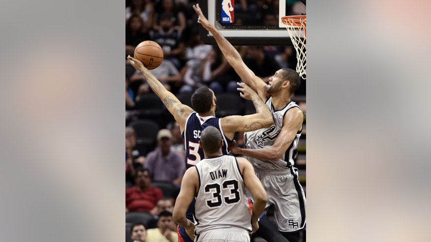 Atlanta Hawks' Mike Scott, center, tries to shoot between San Antonio Spurs' Tim Duncan, right, and Boris Diaw, of France, during the first half of an NBA basketball game, Saturday, April 6, 2013, in San Antonio. (AP Photo/Darren Abate)