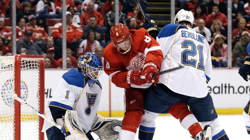 St. Louis Blues center Patrik Berglund (21), of Sweden, defends Detroit Red Wings left wing Justin Abdelkader (8) in front of goalie Brian Elliott (1) in the second period of an NHL hockey game in Detroit, Sunday April 7, 2013. (AP Photo/Paul Sancya)