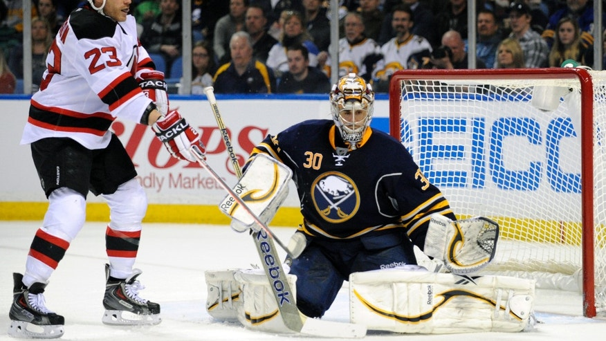 New Jersey Devils'  right winger David Clarkson (23) watches the puck rebound off the pad of Buffalo Sabres' goaltender Ryan Miller (30) during the second period of an NHL hockey game in Buffalo, N.Y., Sunday, April 7, 2013. (AP Photo/Gary Wiepert)