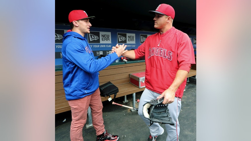 Johnny Manziel, left, Heisman Trophy winner and Texas A&M quarterback, shakes hands with Los Angeles Angels center fielder Mike Trout in the dugout during warmups before a baseball game between the Angels and the Texas Rangers, Sunday, April 7, 2013, in Arlington, Texas. (AP Photo/LM Otero)