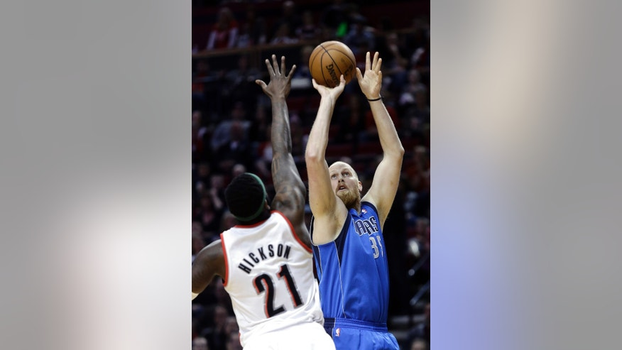 Dallas Mavericks center Chris Kaman, right, shoots over Portland Trail Blazers center J.J. Hickson during the first quarter of an NBA basketball game in Portland, Ore., Sunday, April 7, 2013.(AP Photo/Don Ryan)