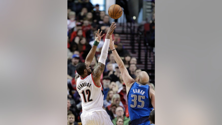 Portland Trail Blazers forward LaMarcus Aldridge, left, shoots over Dallas Mavericks center Chris Kaman during the first quarter of an NBA basketball game in Portland, Ore., Sunday, April 7, 2013.(AP Photo/Don Ryan)