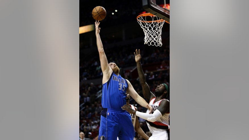 Dallas Mavericks center Chris Kaman (35) shoots over Portland Trail Blazers center J.J. Hickson during the first quarter of an NBA basketball game in Portland, Ore., Sunday, April 7, 2013. (AP Photo/Don Ryan)