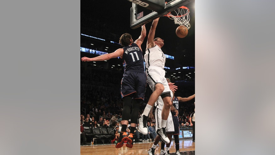Brooklyn Nets' Brook Lopez, front right, scores a basket past Charlotte Bobcats' Josh McRoberts, front left, during the first half of an NBA basketball game on Saturday, April 6, 2013, in New York. (AP Photo/Mary Altaffer)