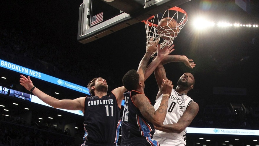 Brooklyn Nets' Andray Blatche (0) scores a goal past Charlotte Bobcats' Josh McRoberts (11) and Tyrus Thomas during the first half of an NBA basketball game on Saturday, April 6, 2013, in New York. (AP Photo/Mary Altaffer)