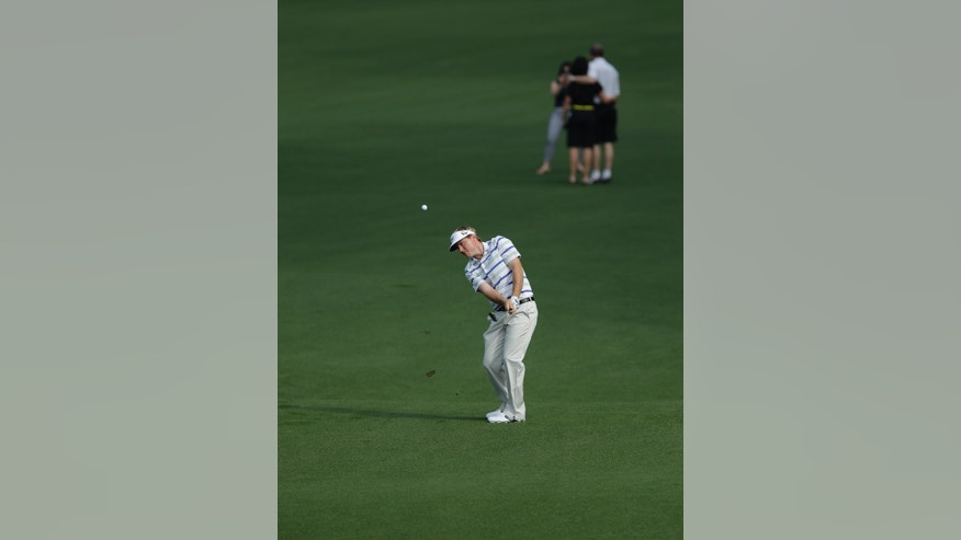 Russell Henley hits on the second hole while spectators stop to take photos on the second fairway during a practice round for the Masters golf tournament Monday, April 8, 2013, in Augusta, Ga. (AP Photo/Matt Slocum)