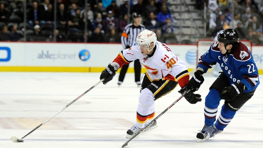 Calgary Flames left wing Alex Tanguay, left, brings the puck up against Colorado Avalanche defenseman Matt Hunwick, right, in the first period of an NHL hockey game on Monday, April 8, 2013, in Denver. (AP Photo/Chris Schneider)