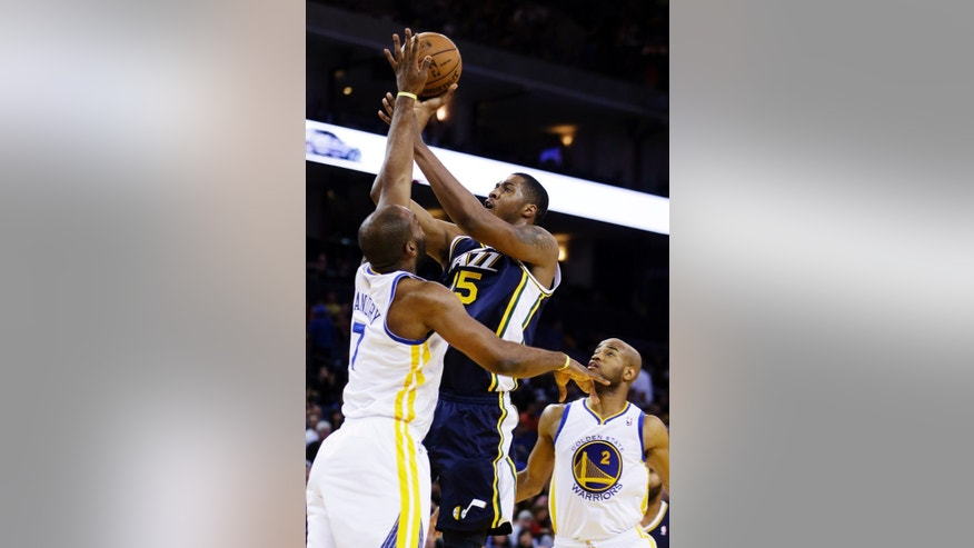 Utah Jazz's Derrick Favors (15) shoots over Golden State Warriors' Carl Landry during the first half of an NBA basketball game, Sunday, April 7, 2013, in Oakland, Calif. (AP Photo/Ben Margot)