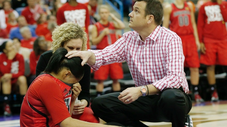 Louisville head coach Jeff Walz talks to Louisville forward Monique Reid (33) after her injury  in the first half of a national semifinal at the Women's Final Four of the NCAA college basketball tournament, Sunday, April 7, 2013, in New Orleans. (AP Photo/Dave Martin)