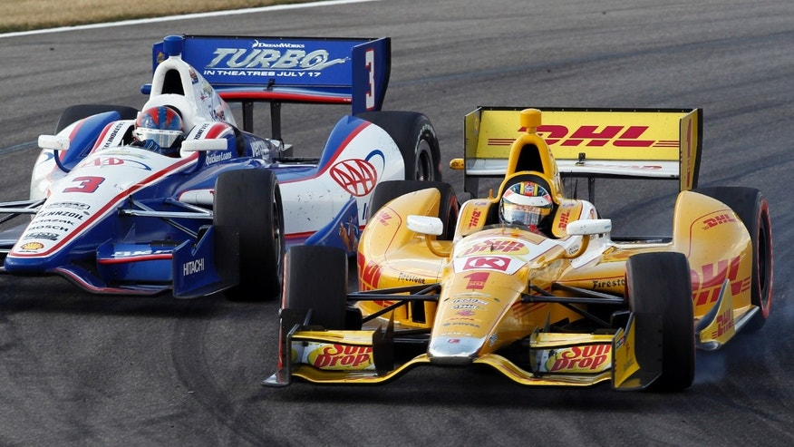 Ryan Hunter-Reay (1) passes Helio Castroneves (3), of Brazil, during the IndyCar Series Grand Prix of Alabama auto race in Birmingham, Ala., Sunday, April 7, 2013. (AP Photo/Butch Dill)