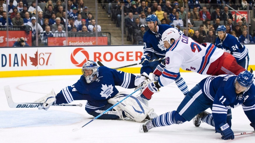 Toronto Maple Leafs goalie James Reimer, left, makes a diving save on a shot by New York Rangers forward Ryane Clowe, second from right, as Maple Leafs forward Jay McClement, right, trips up Clowe during the third period of their NHL hockey game in Toronto, Monday, April 8, 2013. (AP Photo/The Canadian Press, Nathan Denette)